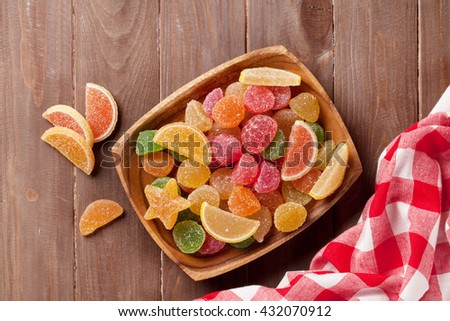 Colorful marmalade on wooden background. Top view - stock photo