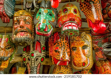 colorful mayan wooden masks hanging guatemala market - stock photo
