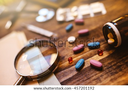 Colorful medical tablets and pills scattered on doctor's office desk, healthcare and medicine concept image, selective focus - stock photo