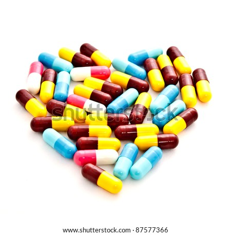 colorful medicine pills placed in heart shape on white background