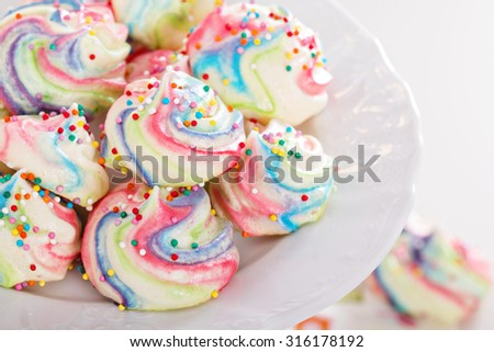 Colorful meringues painted rainbow colors with sprinkles