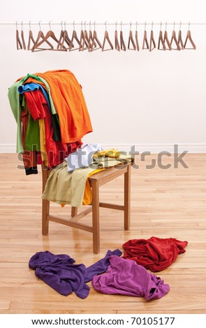 Colorful messy clothes on a chair and row of empty hangers on the background. - stock photo