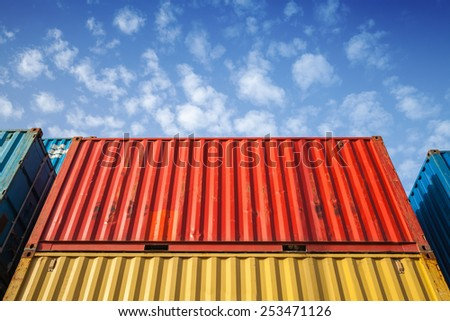 Colorful metal Industrial cargo containers are stacked in the storage area under blue cloudy sky - stock photo