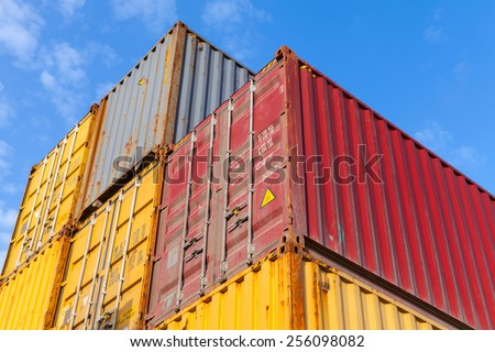 Colorful metal industrial cargo containers are stacked in the storage area under blue sky - stock photo