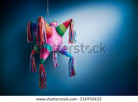 Colorful mexican pinata used in birthdays on a blue background - stock photo