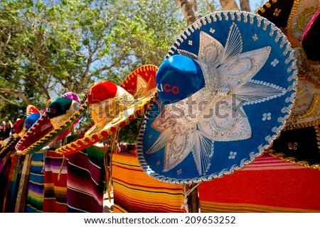 colorful Mexican sombreros and ponchos lined up outdoors - stock photo