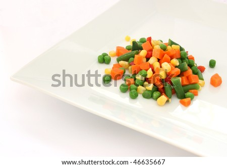 Colorful mix of cooked vegetable on white plate - pea, corn, carrot and green bean - stock photo