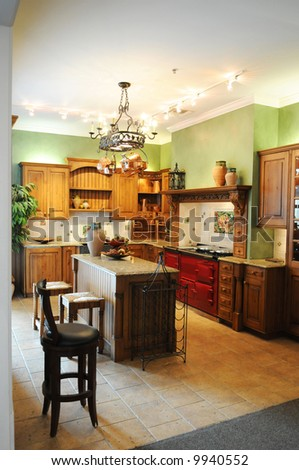 Colorful modern kitchen with wooden cabinets and red stove - stock photo