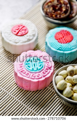 Colorful moon cake and lotus seeds on nature background - stock photo
