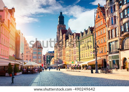 Colorful morning scene on Wroclaw Market Square with St. Elisabeth church. Sunny cityscape in historical capital of Silesia, Poland, Europe. Artistic style post processed photo.
