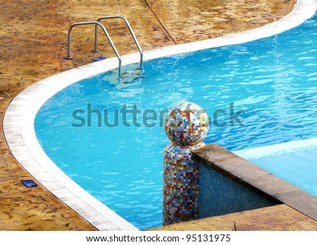 Colorful mosaic sphere in swimming pool glistening calm pool - stock photo