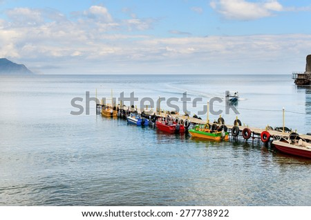 Colorful Motor Boats Tied Up Along Wooden Dock in Lake with Approaching Boat Beneath Blue Sky with Clouds - stock photo