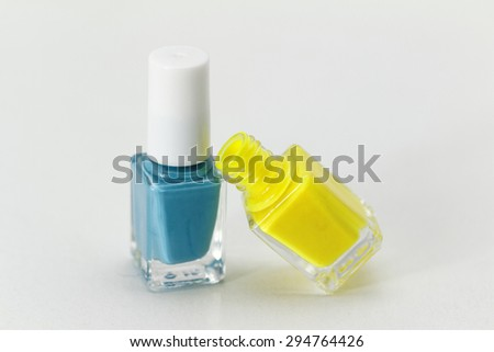 Colorful nail polish - white background, yellow and blue style - stock photo