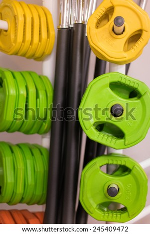 Colorful new weights for bodybuilding in a gym or shop hanging on rods in different sizes and weights - stock photo
