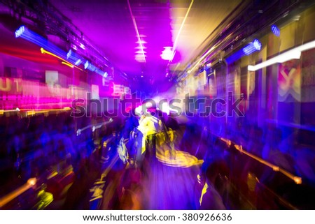 Colorful night club party lights in motion blur, people dancing - stock photo