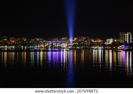 Colorful night seascape of a coastal resort city with a numerous of lights and glares. Cosy night bay with the colorful reflections on the water surface