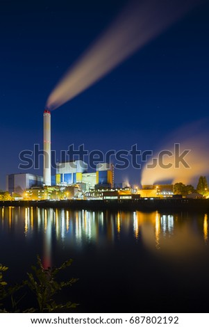 Colorful night view of a modern waste incineration plant in Oberhausen, Germany with deep blue sky.
