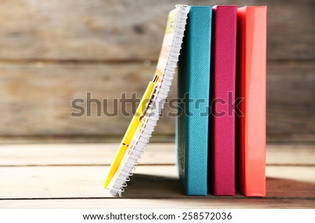 Colorful notebooks and pen on old wooden table - stock photo