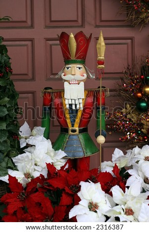 colorful nutcracker surrounded by poinsiettas and other xmas decorations