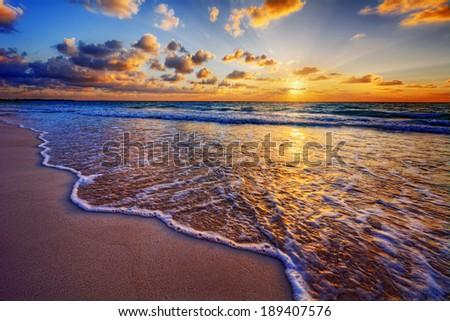 Colorful ocean beach sunrise with deep blue sky and sun rays - stock photo