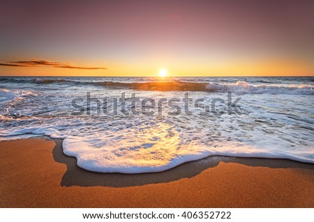 Colorful ocean beach sunrise with deep blue sky and sun rays. - stock photo