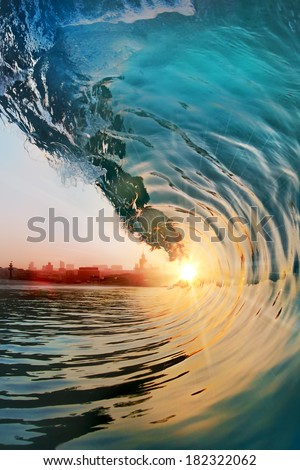 colorful ocean wave closing near a city beach at sunset time  - stock photo