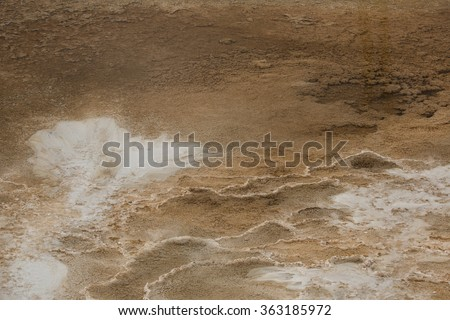 Colorful, orange geothermal pools of hot water with white carbonate deposits and ridges, overlying the travertine rock of Mammoth Hot Springs in Yellowstone National Park, Wyoming. - stock photo