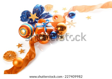 Colorful orange, gold and blue Xmas background over white with copyspace in a corner arrangement of baubles, ribbon, star, bow and gifts - stock photo