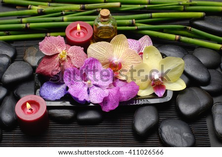 colorful orchid ,stones,oil,bamboo grove,candle on mat background   - stock photo