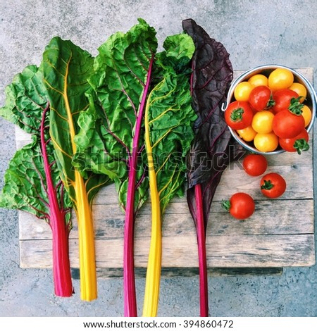 Colorful organic veggies, rainbow swiss chard, cherry tomatoes and cape gooseberry on wooden table. - stock photo