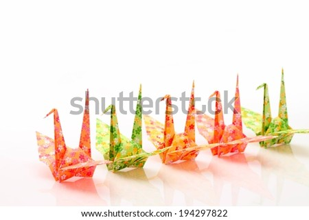 Colorful origami cranes lined up in a row. - stock photo