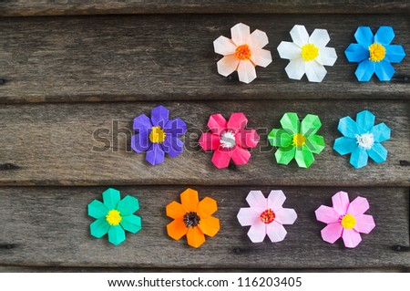 Colorful origami flower on wooden wall