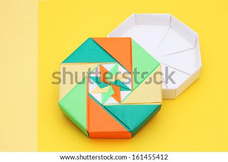 colorful origami paper box on a yellow background - stock photo