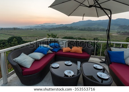 Colorful Outdoor Sofa Chair Dinner Table under Umbrella Lounge Bar Cafe Restaurant Terrace in Luxury Hotel Resort Spa with mountains view background at Dusk Evening Summer Sunset, Chiang Rai, Thailand - stock photo