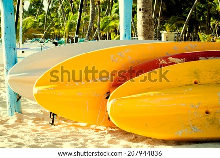 Colorful paddle boards on the  beach in Punta Cana, Dominican Republic. Summer vacation and water sports concept - stock photo