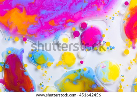 Colorful paint drops mixed in liquid on white background - stock photo