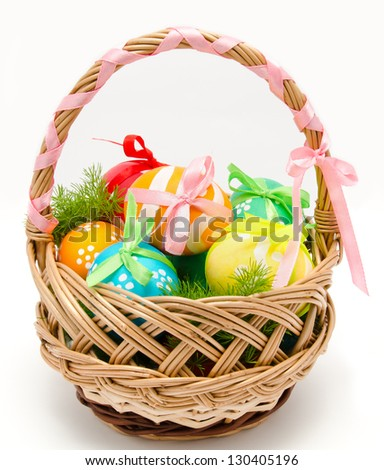 Colorful painted easter eggs in basket isolated over white - stock photo
