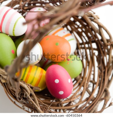 Colorful painted easter eggs in brown basket - stock photo