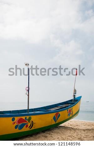 Colorful painted fishing boat on Mahabalipuram beach, India - stock photo