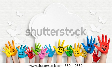 colorful painted hands in front of a decorated wall with a flower and butterflies - stock photo
