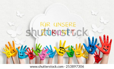 "colorful painted hands in front of a decorated wall with the sentence ""For our future"" in German - stock photo"