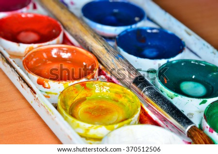 Colorful palette with watercolors and paint brushes - stock photo