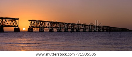 Colorful panoramic landscape of a beautiful  sunset at Bahia Honda state park in Florida and the old historic landmark, the Flagler railway bridge that used to connect Miami and Key West. - stock photo