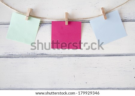 Colorful paper cards hanging on clothespins - stock photo