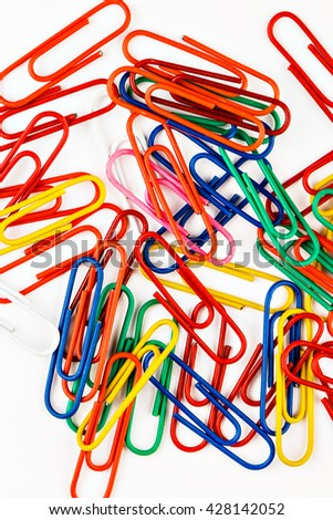 Colorful paper clips on white background. Vertical image.