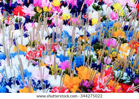 Colorful paper flowers with incense