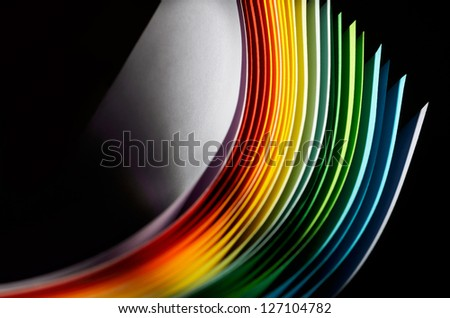 Colorful paper section in elliptical shapes on black background - stock photo