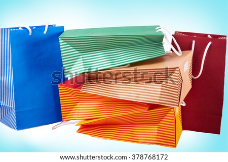 Colorful paper shopping bags against gradient blue background