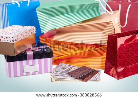 Colorful paper shopping bags and boxes with money and debit cards against blue background - stock photo