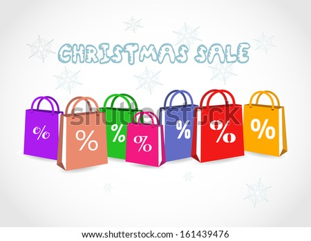 Colorful paper shopping bags with discount sign on a light grey background - Christmas Sale